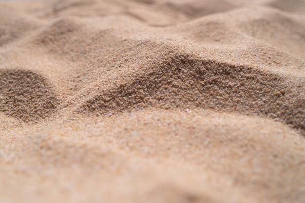 De bruine achtergrond van de zandtextuur van fijn zand met natuurlijke lijngolf erop.