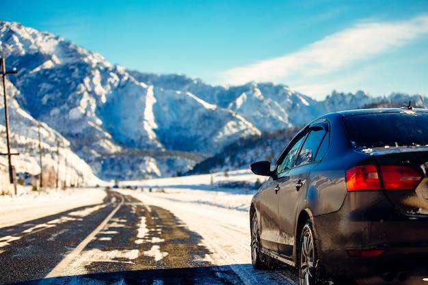 De bruine auto in de bergen de weg