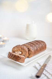 De bruine cake van het chocoladesponsbroodje met room die op plaat met mes op textielhanddoek met kaarsen wordt gediend