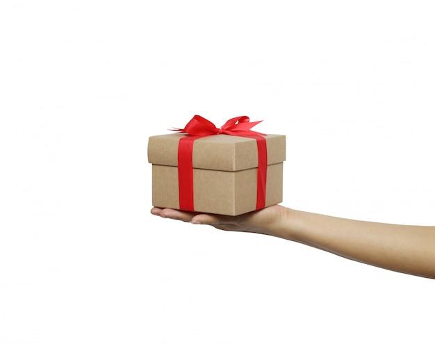 De bruine doos van de kerstmisgift op de hand van een vrouw die op witte achtergrond wordt geïsoleerd.