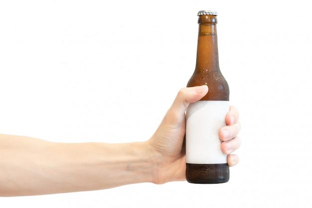 De bruine fles van het glasbier met wit leeg etiket in de hand van mensen die op wit wordt geïsoleerd