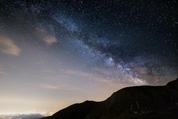 De buitengewone schoonheid en helderheid van de melkweg en de sterrenhemel gevangen vanaf grote hoogte in de zomer op de alpen met gloeiende vallei beneden en lichtvervuiling.