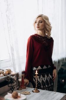 De buitensporige blondevrouw gekleed in rode kleren bevindt zich in een ruimte met kerstmisdecor