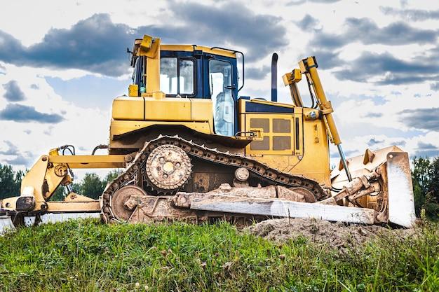 De bulldozermachine egaliseert de bouwplaats. grondverzetmachine met tractor beweegt aarde. detailopname. bouw zware machines.