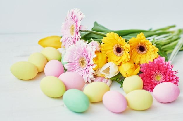 De cake, de eieren en de konijnen van pasen met verse bloemen op de lijst, de keuken zijn verfraaid voor pasen