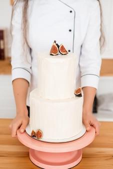 De cake is op twee niveaus in handen van de chef. witte bruidstaart met vijgen