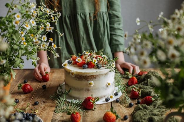 De cake is versierd met bessen en bloemen