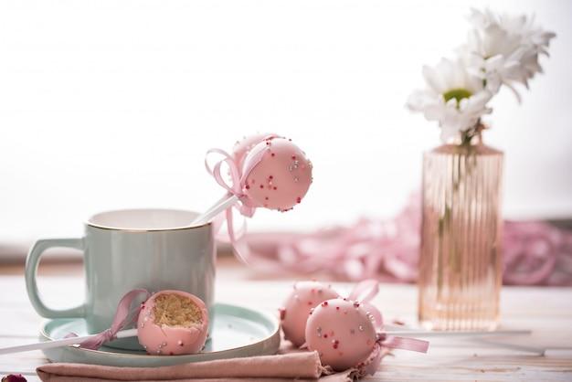 De cake springt in een lichte sleutel in een mooi werktuig met roze chocoladeroom en bloemen op een houten achtergrond.