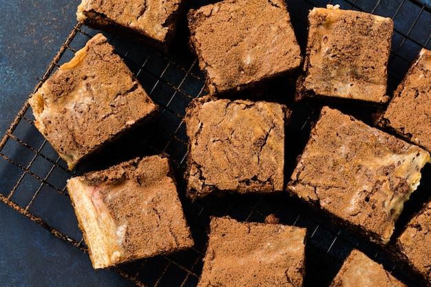 De cake van de browniekaastaart met kers en chocolade op donkere achtergrond. bovenaanzicht.