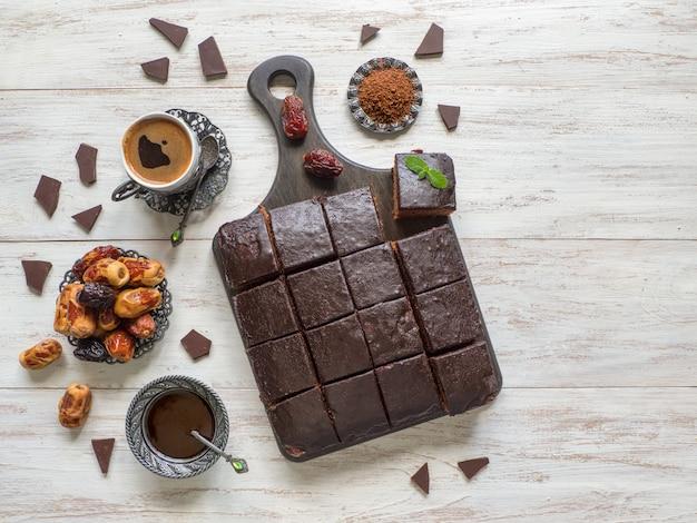 De cake van de chocoladebrownie, dessert op witte houten lijst