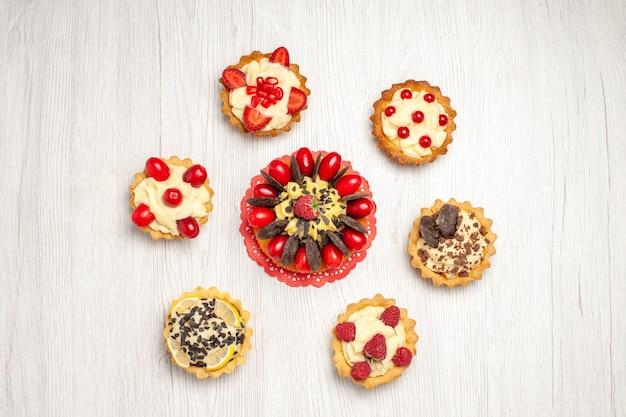 De cake van de hoogste meningsbes op het rode ovale kanten kleedje en taarten op de witte houten grond