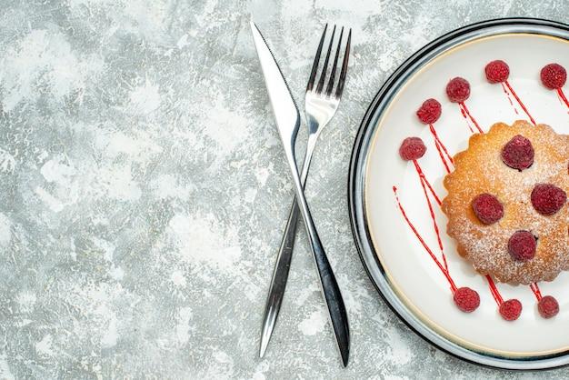 De cake van de hoogste meningsbes op witte ovale plaatvork en dinermes op grijze oppervlakte vrije ruimte