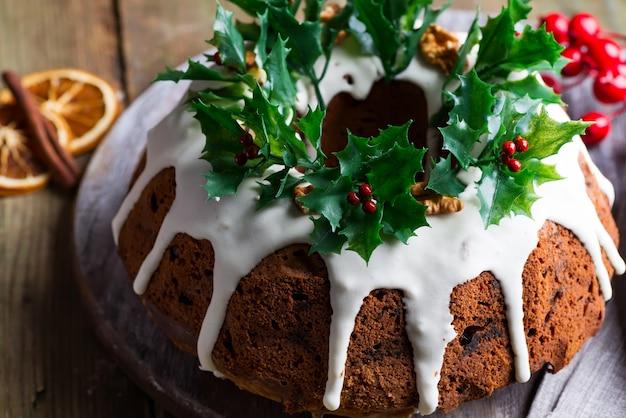 De cake van de kerstmischocolade met witte suikerglazuur en granaatappelpitten op houten dark