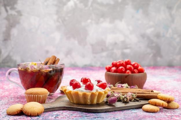 De cake van de vooraanzichtroom met verse rode amerikaanse veenbessen samen met kaneelkoekjes en thee op het heldere bureausnoepje