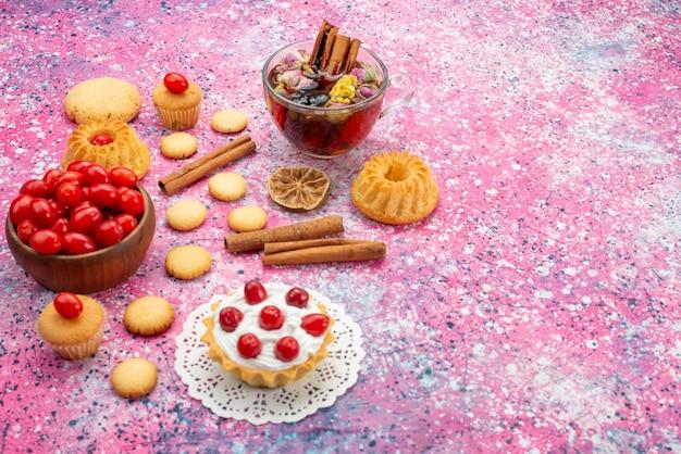 De cake van de vooraanzichtroom met verse rode amerikaanse veenbessen samen met kaneelkoekjes en thee op het heldere zoete fruit van het bureaukoekje