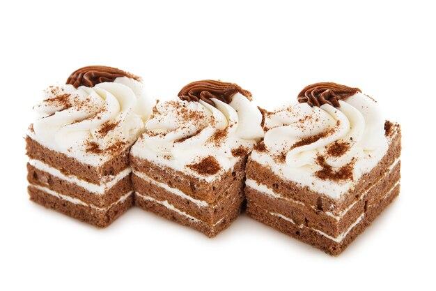De cake van het chocoladekoekje die met geïsoleerde roombloemen wordt verfraaid