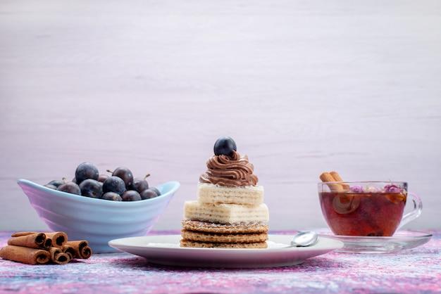 De cakes van de vooraanzichtwafel met druivenkaneel en thee op grijs