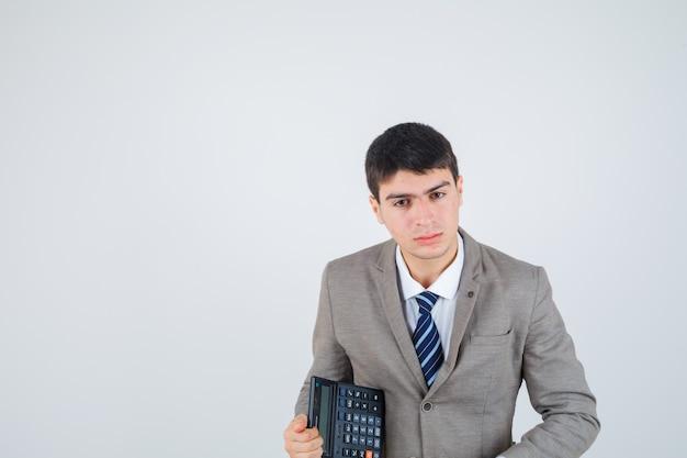 De calculator van de jonge jongensholding in formeel kostuum en leuk, vooraanzicht kijkt.