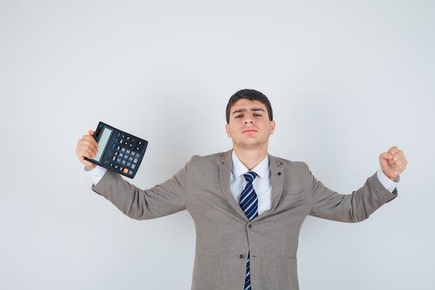 De calculator van de jonge jongensholding, winnaargebaar in formeel kostuum toont en gelukkig kijkt. vooraanzicht.