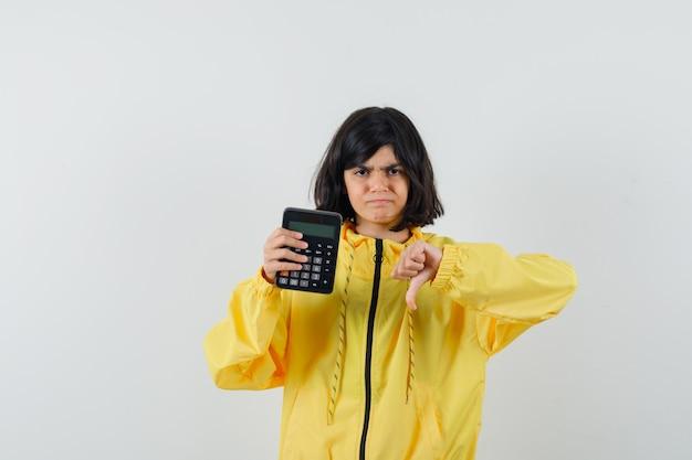 De calculator van de meisjesholding, die duim in gele hoodie toont en teleurgesteld, vooraanzicht kijkt.