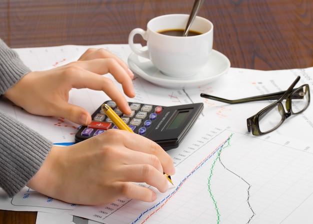 De calculator van onderneemsteranalyzing financial report with bij houten bureau