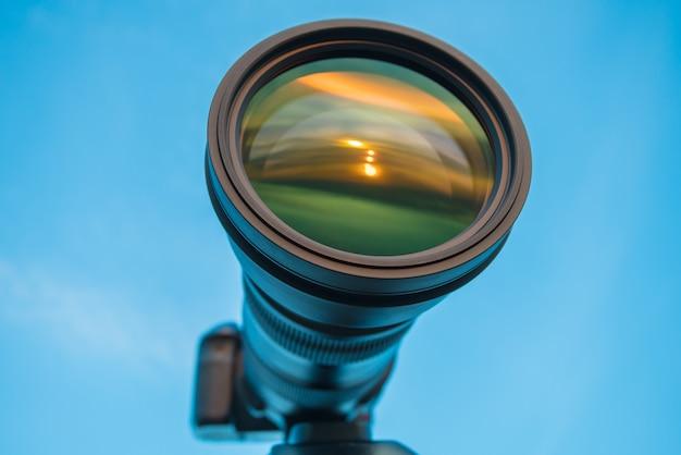 De camera met een grote lens op de achtergrond van de lucht