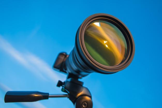 De camera met een statief op de blauwe hemelachtergrond