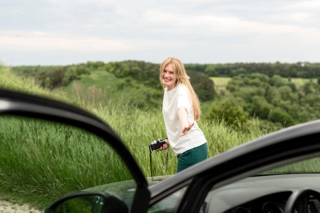 De camera van de vrouwenholding en het stellen voor auto