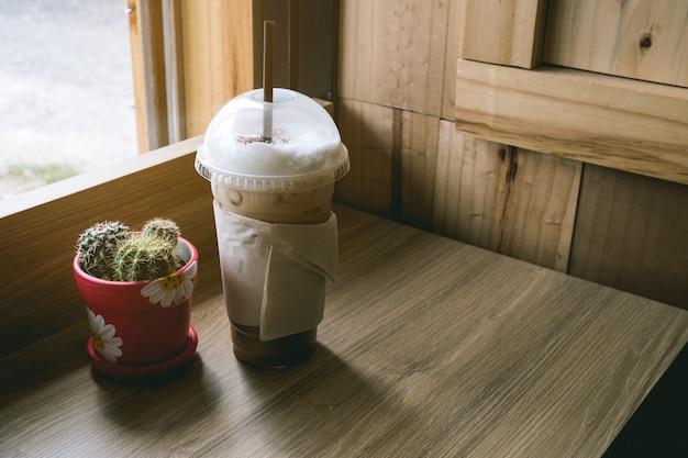 De cappuccinokoffie van het ijs op houten vloer, naast venster