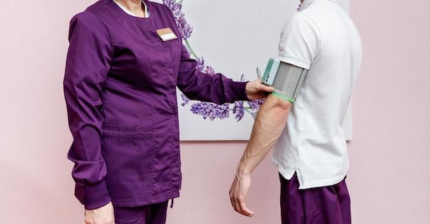 De cardioloog controleert de bloeddruk bij de patiënt