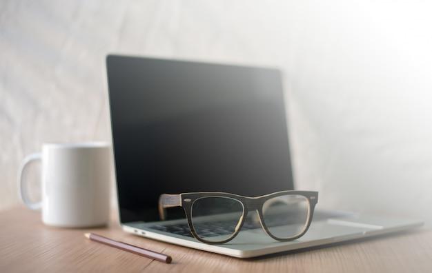 De carrière van de schrijver op het bureau met witte koffiemokken, notitieboekjes, potloden, glazen
