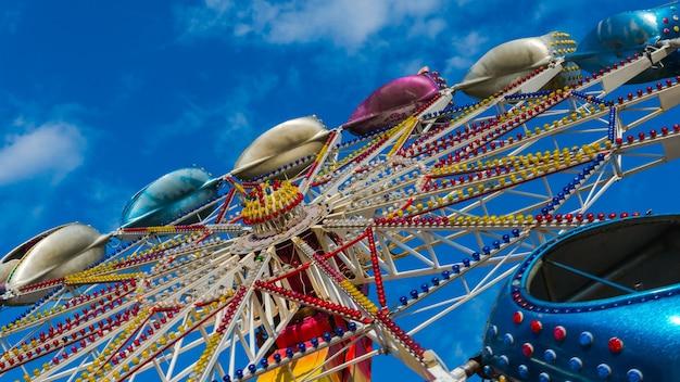 De carrousel in het pretpark draait tegen de blauwe lucht pretpark voor kinderen