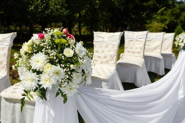 De ceremoniedecoratie van het huwelijk in een park. bloemboeket dicht omhoog