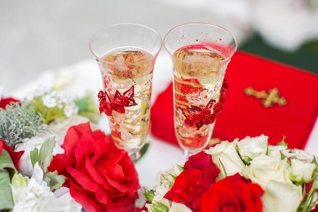 De champagneglazen. huwelijksceremonie buitenshuis. boeket met rode bloemen.