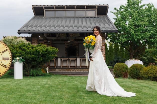 De charmante bruid houdt een bruidsboeket en loopt langs de tuin
