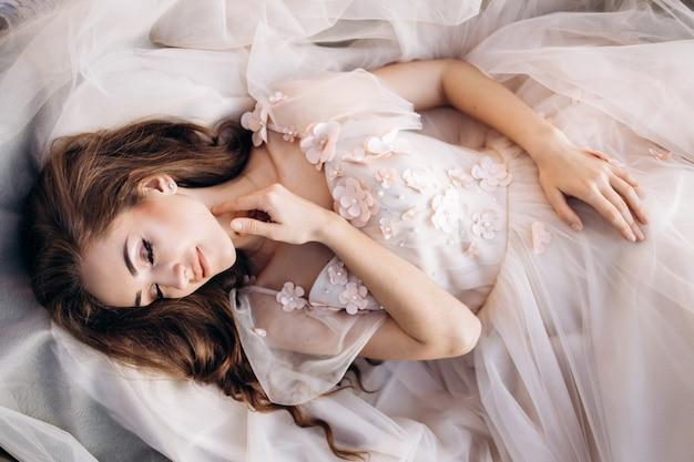 De charmante bruid ligt op de trouwjurk