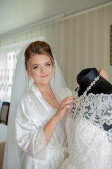 De charmante bruid met bruidsmeisjes staat in de buurt van trouwjurk. de voorbereiding van de ochtend van het bruids huwelijk.