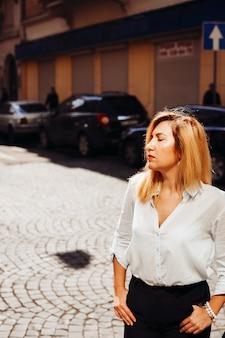 De charmante dame die op straat staat