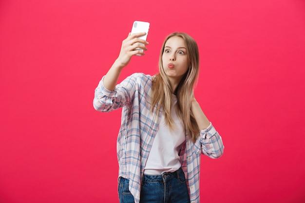 De charmante jonge vrouw in witte hoedenreis en neemt selfie