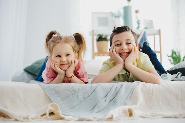 De charmante kleine jongen en het meisje liggen op het bed