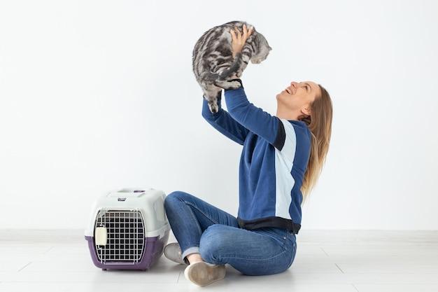 De charmante positieve jonge vrouw houdt in haar handen haar mooie grijze zitting van de vouwen schotse kat Premium Foto