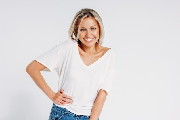 De charmante vriendschappelijke blonde glimlachende vrouw 35 jaar die in witte t-shirt en jeans camera bekijken die op witte achtergrond wordt geïsoleerd, bespot omhoog