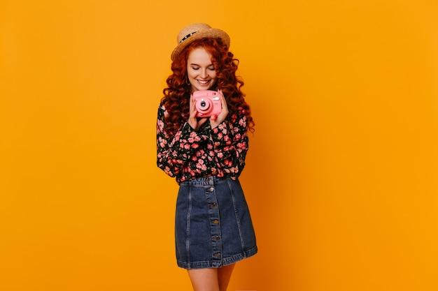 De charmante vrouw met glimlach houdt roze minicamera vast. dame in stijlvolle denim outfit en strooien hoed poseren in oranje studio.