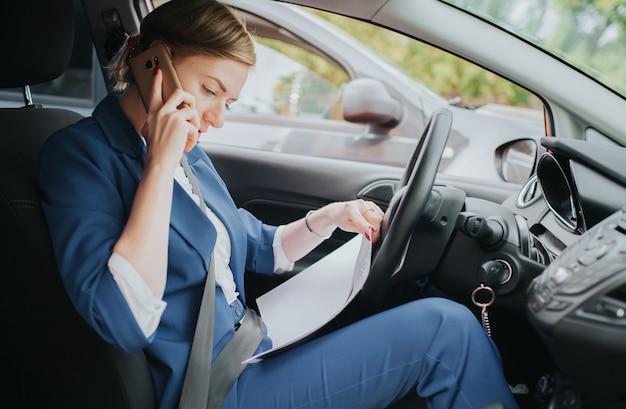 De chauffeur gaat op pad, telefoneert en werkt tegelijkertijd met documenten. zakenvrouw meerdere taken uitvoeren. multitasking zakenman.