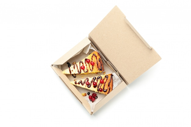 De cheesecake haalt binnen doos weg die op witte achtergrond wordt geïsoleerd