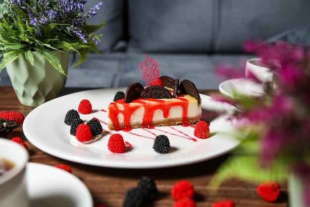 De cheesecake van de zijaanzichtaardbei met chocoladeschilferkoekjes en braambes en frambozenmarmelade op een plaat