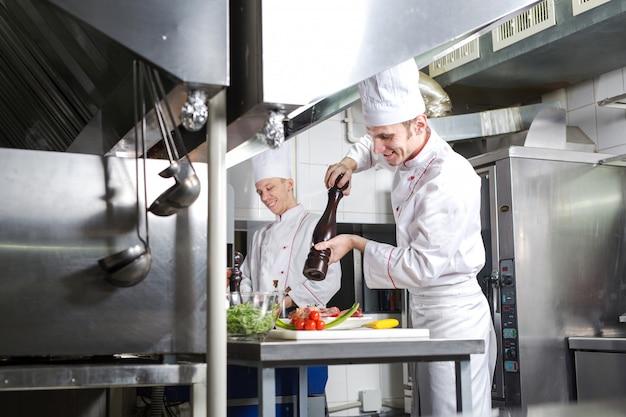 De chef bereidt een gerecht in de keuken van restoran.