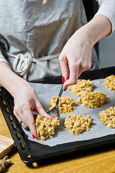 De chef bereidt koekjes, spreid het deeg op de trays.