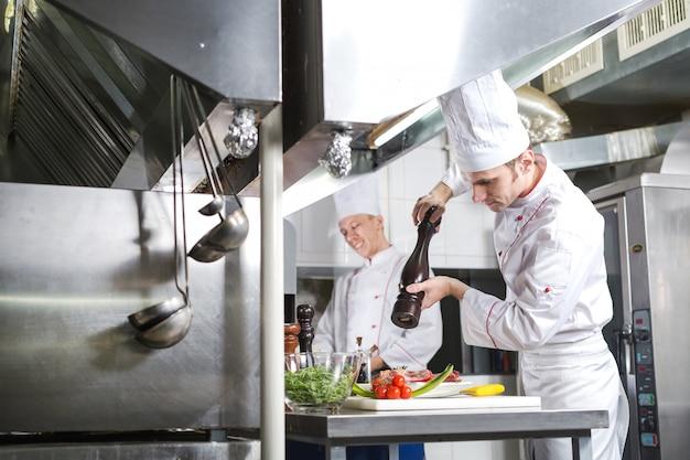 De chef-kok bereidt een gerecht in de keuken van restoran.