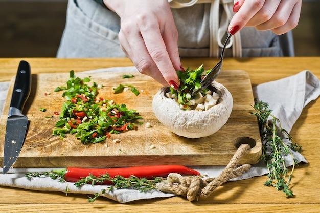 De chef-kok bereidt gevulde champignons